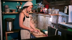 Positive woman slicing green onion in the kitchen Stock Footage