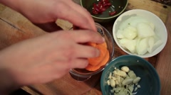 Woman adding sliced carrot into a glass bowl - stock footage