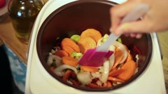 Woman hands stirring vegetables in Multicooker Stock Footage