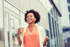 happy african businesswoman with coffee in city - stock photo