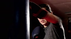beutiful woman trains her hits on a punching bag, slow motion 1 - stock footage