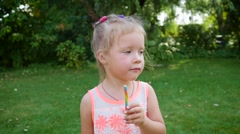 Little child girl eat kiss lips a sweet colored caramel candy stick in garden - stock footage