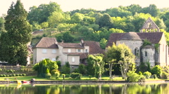 Joggers along river bank, Dordogne River at Beaulieu sur Dordogne Stock Footage