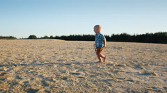 Steadicam shot: Cool kid running across the sand, rejoices. Slow-motion video Stock Footage