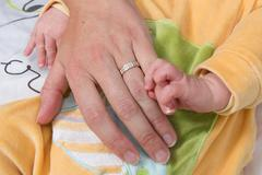 Parents Holding Newborn Kid. Child Hand Closeup into Parents - stock photo