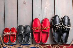 Family boat shoes on wooden background. Four pair of red and black boat shoes on - stock photo