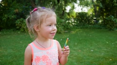 Little child girl eat suck with lips a sweet colored caramel candy stick Stock Footage