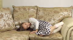 Beautiful little girl lies down on the sofa before going to sleep Stock Footage