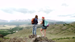 Two woman wanderers exploring map while sitting on a mountain hill in sunny Stock Footage