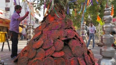 Man throwing color powder on pile dung for Holi festival,Ujjain,India Stock Footage