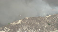 Firehawk helicopter makes low approach and water drop (Sand Fire) Stock Footage