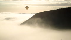 Balloon floating above morning mist, Castelnaud, Dordogne, Aquitaine Stock Footage