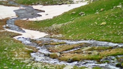 Stream in at green hill in High Snowy Mountains with Clouds. Kavkaz region Stock Footage