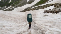 Tourist with Hiking backpacks coming down the High Snowy Mountains in Kavkaz Stock Footage