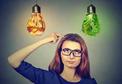 Woman thinking looking up at junk food and green vegetables light bulbs Stock Photos