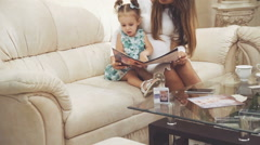 Pretty woman with little girl sitting in comfortable room, looking on magazine - stock footage