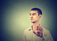 Annoyed angry man with bad attitude giving talk to hand gesture Stock Photos
