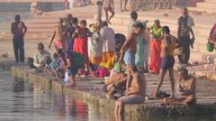 Pilgrims washing and woman puts candle in river,Ujjain,India Stock Footage