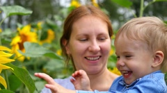 The child in his mother's arms playing with flower Stock Footage