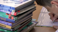 Student bent over textbooks makes recording ballpoint pen in a notebook Stock Footage