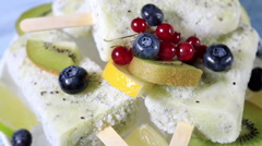 Popsicles with berries and fruit on a wooden table Stock Footage