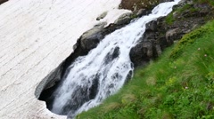 Mountain Waterfall flowing Under Ice. Melting of the glacier in Spring Stock Footage