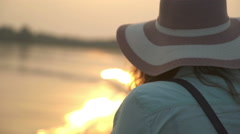 Beautiful girl in broad-brimmed hat in the setting sun Stock Footage