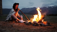 The girl in a warm sweater sitting by the fire in the evening - stock footage