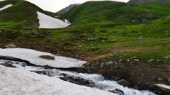Stream in at green hill in High Snowy Mountains with Clouds. Kavkaz region - stock footage