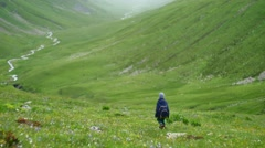 Little boy with backpack hiking in scenic green mountains valley and river Stock Footage