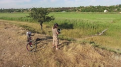 Aerial video cyclist with remote control launches drone circled around him Stock Footage
