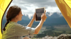 Tablet pc - camping woman taking picture photo selfie selfportrait at campsite - stock footage