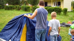 A man with kids gathering tent Stock Footage