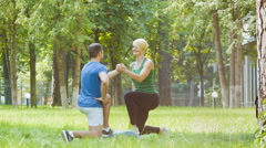 Sporty young woman and man or instructor doing gymnastic exercise outdoor Stock Footage