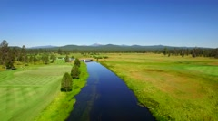 Aerial view of water by golf course and mountains in Oregon 3 Stock Footage