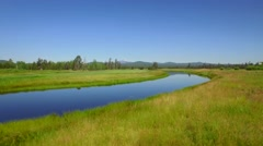 Aerial view of water by golf course and mountains in Oregon 8 Stock Footage