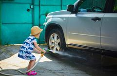 Little girl helps her parents to wash the car Stock Photos