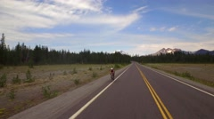 Drone shot of bike rider by Oregon mountainside under blue sky 4 Stock Footage