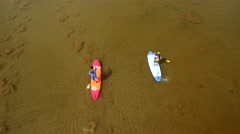 Aerial view of paddle boarders riding across lake 2 Stock Footage
