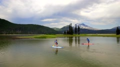 Aerial view of paddle boarders on lake next to green trees and mountainside 2 Stock Footage
