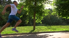 Athletic man in white tshirt running in park against sun and trees. Slow motion Stock Footage