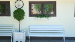 Retro bench outside old Italian house with clock Stock Footage