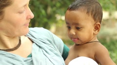 Western woman plays with small Indian baby,  close up narrow depth of field Stock Footage