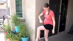 Young Pregnant Woman Sprays Bug Repellent on Herself Before Going Outdoors Stock Footage
