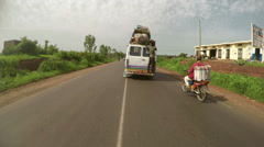 A van traveling with a man hanging behind. Camera car in Africa. N. Stock Footage