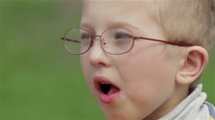 Boy in glasses eats Stock Footage