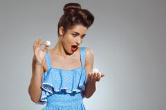 Picture of beautiful pin-up girl holding sweeties in hands at studio Stock Photos