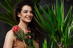 Young beautiful brunette girl in tropical plants over grey background Stock Photos