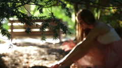Beautiful female touches her long hair in the rays of warm summer sun outside in Stock Footage