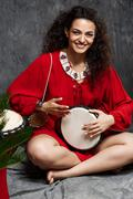 Beautiful girl playing drum in tropical plants over grey background Stock Photos